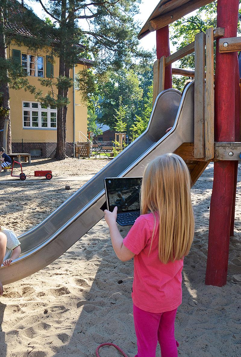 kleines Mädchen mit Tablet in der Hand vor einer Rutsche
